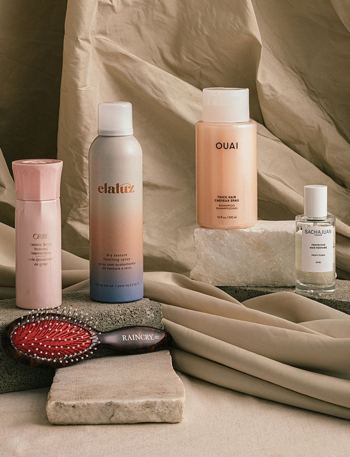 A variety of hair products sit on stones and draped cloth. Shop Hair.