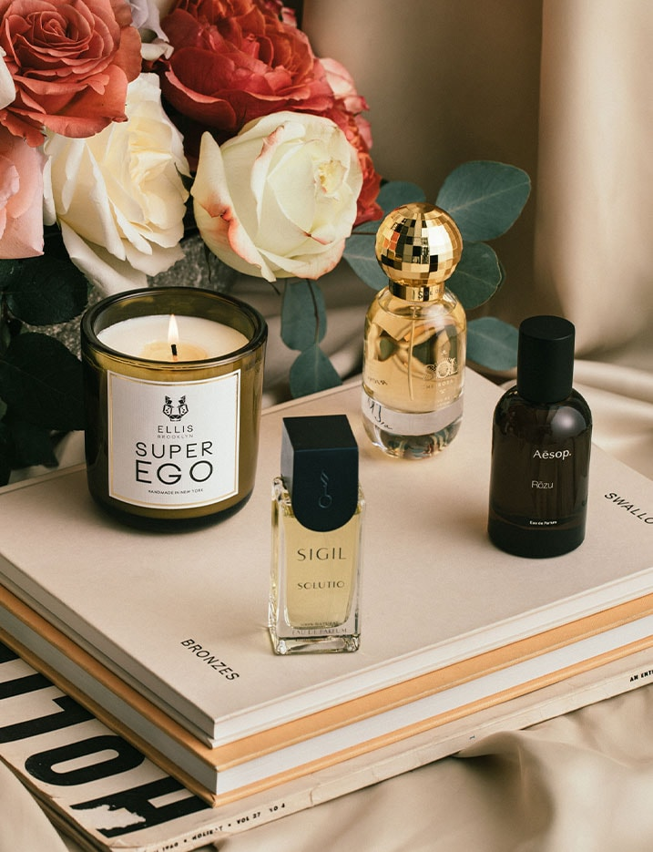 A variety of fragrances in candle and bottled oil form sit on a table of roses and books. Shop Fragrance.