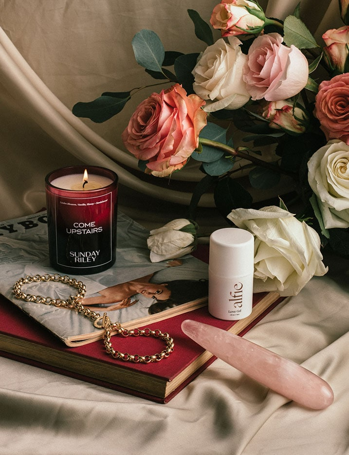 A variety of sexual wellness products sit on a table with roses and books. Shop Sexual Wellness.
