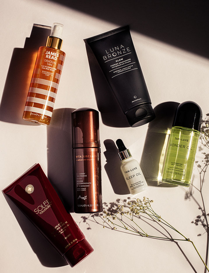 Variety of self-tanning skincare products lay on a tabletop. Shop Self-Tanning