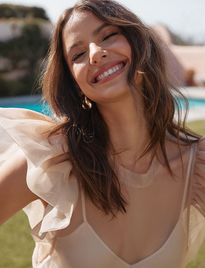 Model smiles widely showing bright white teeth. Shop Teeth Whitening and care.