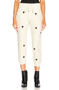 THE GREAT Heart-Print Cropped Cotton Sweatpants in Washed White With Black Hearts