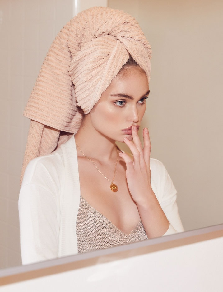 A model with her hair wrapped in a towel applying lip balm while staring in the mirror. Shop Skincare 101.