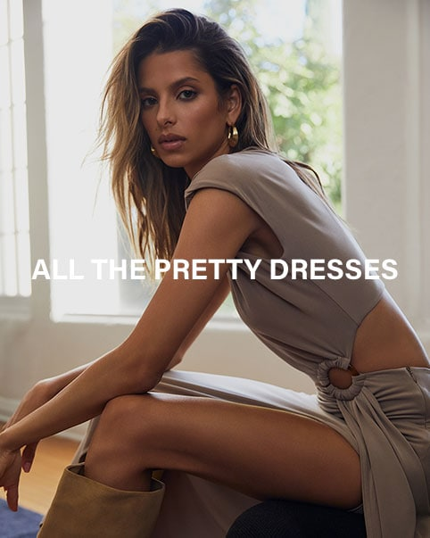 A model standing near an open window wearing a black mini dress with a studded waist and a black cardigan hanging off the shoulders, black tights, and black ankle boots. A model sitting in a chair wearing a taupe colored short sleeve maxi dress with a side ring detail and back cut-out, and tan knee-high boots. All The Pretty Dresses. Shop the Edit.