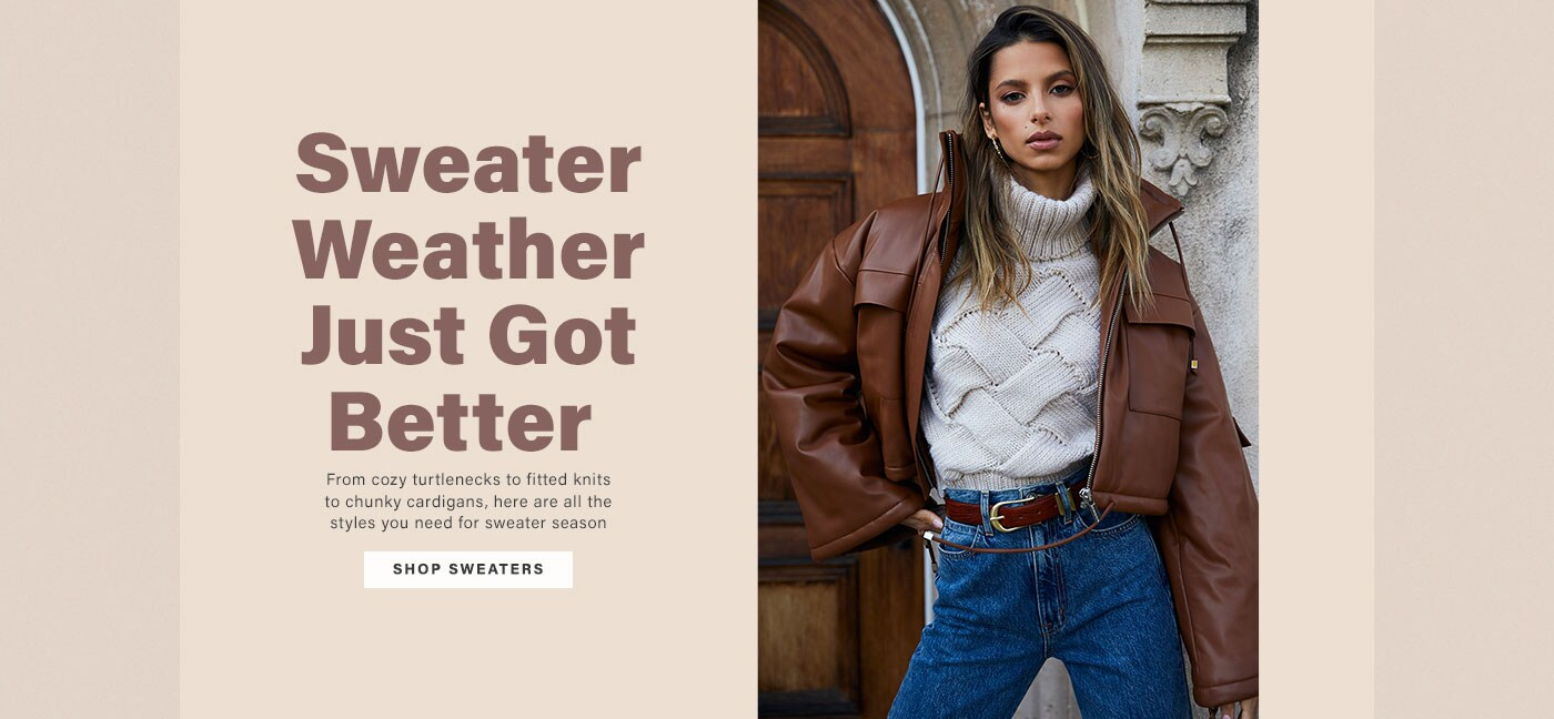 A model standing in front of a door wearing a cream colored turtleneck sweater, a brown leather jacket, blue high waisted jeans with a brown belt. Sweater Weather Just Got Better. Shop Sweaters.