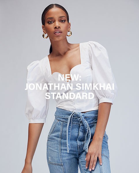 Model wearing Jonathan Simkhai Standard Collection, white shoulder statement top with tied up denim pants.