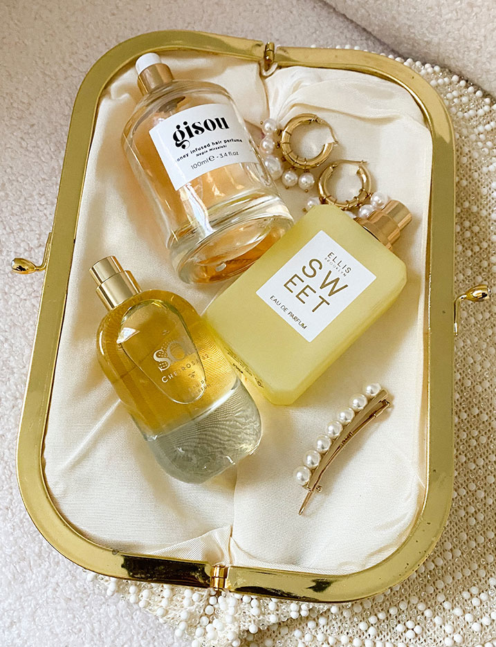 A purse lay open displaying a variety of fragrance sprays, oils, and pearl accessories. SHOP FRAGRANCE