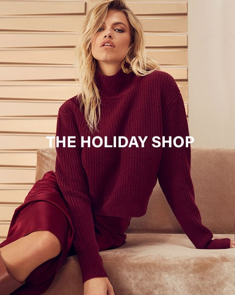 A model sitting on a pink couch wearing a burgundy mock neck sweater and matching skirt. A model sitting on a couch wearing a gold shimmer long sleeve gown with side panel cut-outs and gold heels. A model wearing a white sequined long sleeve crop top with black leather bootcut pants and black pumps. Enter the Holiday Shop.