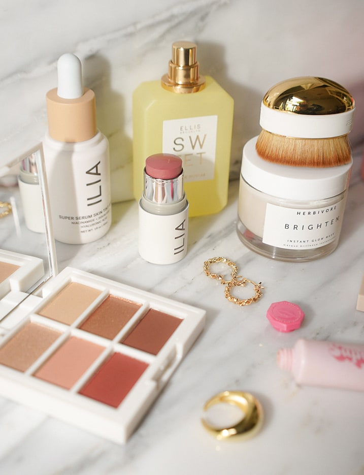 A variety of skincare and makeup products by clean beauty brands are displayed on a marble surface.