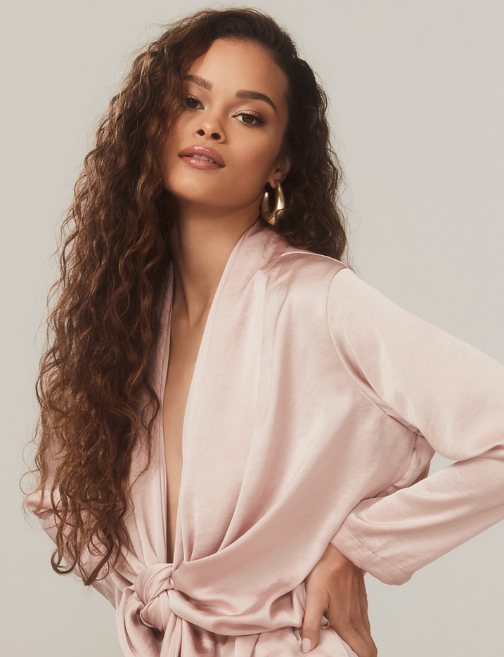 A model with long curly brown hair has her hands on her hips wearing a light pink blouse. Shop Hair.