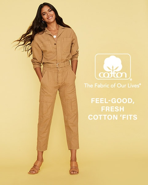 A model wearing a tan jumpsuit. A model kneeling down wearing a white puff sleeve top, blue jeans, and brown flats. A model sitting down wearing a grey matching sweatshirt and sweatpant set and sneakers. A model wearing a black floral print halter midi dress and brown sandals. Fresh Cotton 'Fits. Enter The Cotton Shop