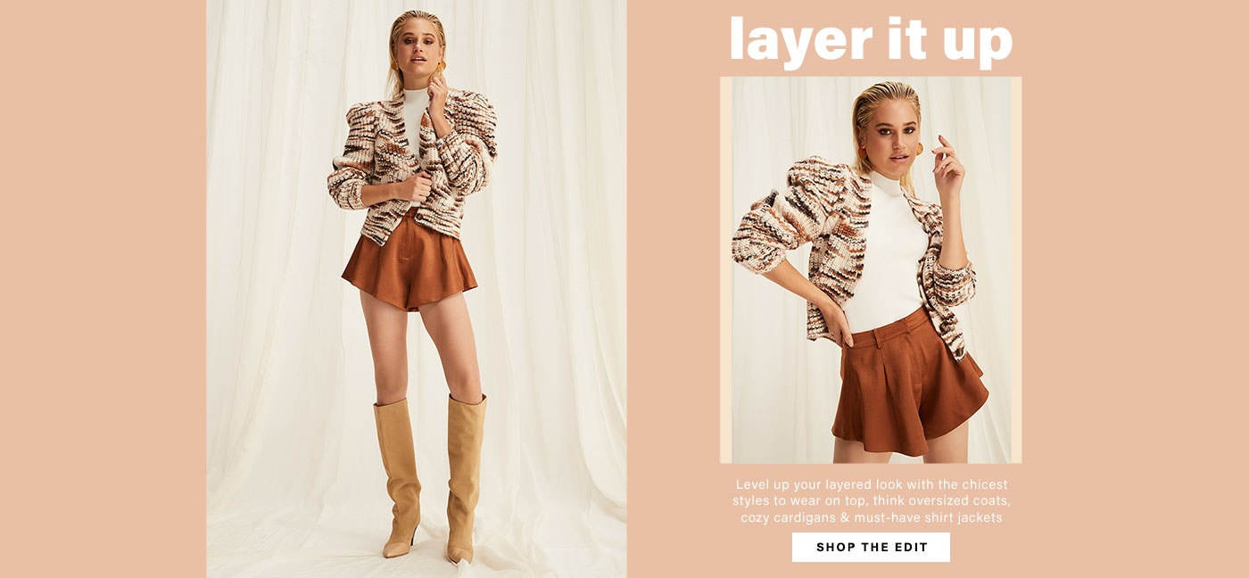 A model wearing a white mock neck top, a neutral tone striped cardigan, brown shorts, and tan knee-high boots. Layer It Up. Shop the Edit.