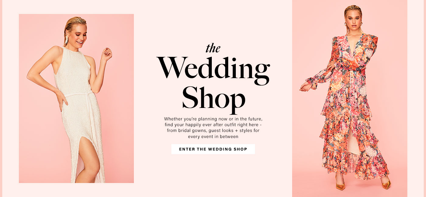 A model wearing a beaded white gown with a waist tie and side slit. A model wearing a floral print long sleeve maxi dress with a ruffle hem and gold heels. The Wedding Shop. Enter The Wedding Shop.