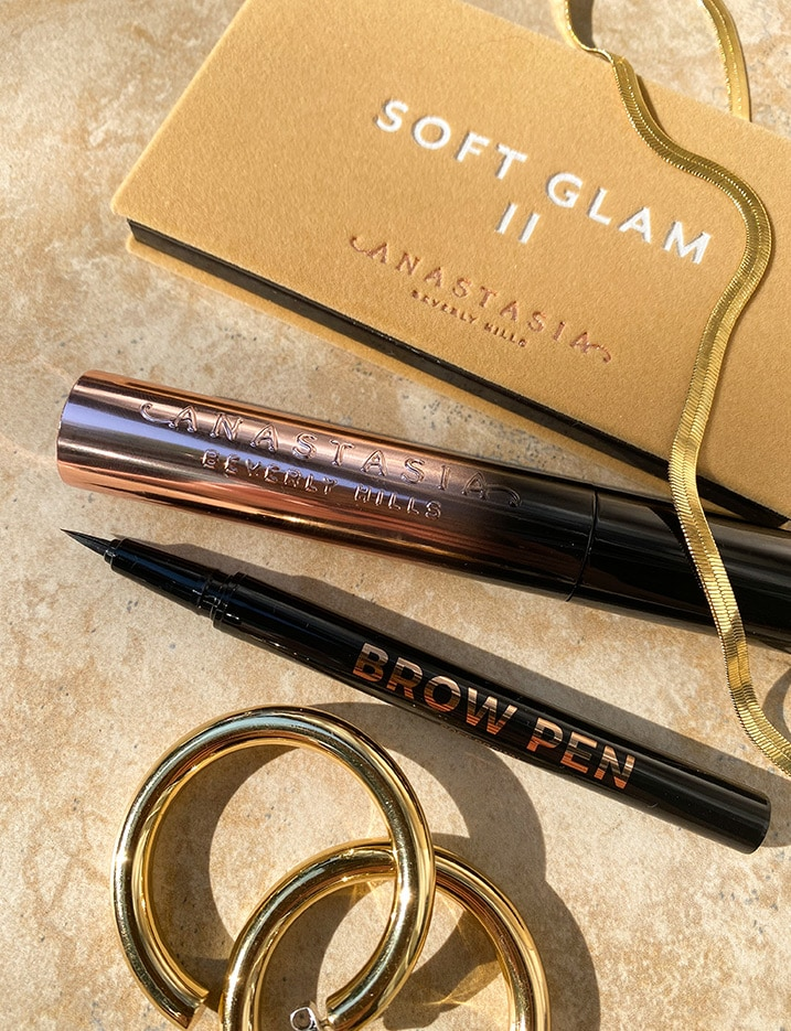 A folded cosmetic case titled Anastasia'S Soft Glam II sits on stone tiles with a few more Anastasia Beverly Hills eye brow products. Shop Makeup.