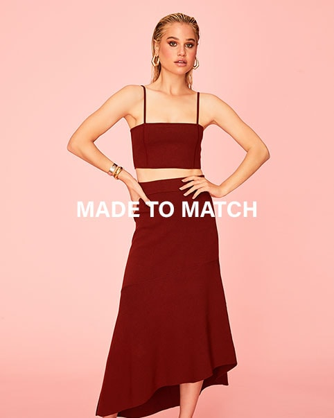 A model posing in front of a pink background wearing a burgundy cami cropped top and matching skirt. Made to Match. The cutest tops + bottoms that were made for each other and your closet. Shop matching sets.
