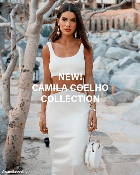 A model wearing a cream-colored mini dress with a ruched front and sash detail. Camila Coelho standing in front of a tree wearing a cream-colored cropped knit tank top and matching maxi skirt with waist cut-outs. Camila Coelho standing on cobblestone stairs wearing a cream-colored maxi dress with front cut-outs. A model standing in front of greenery wearing a cream-colored cropped knit tank top, matching skirt with waist cut-outs, and matching cardigan. NEW Camila Coelho Collection. Shop the Collection.