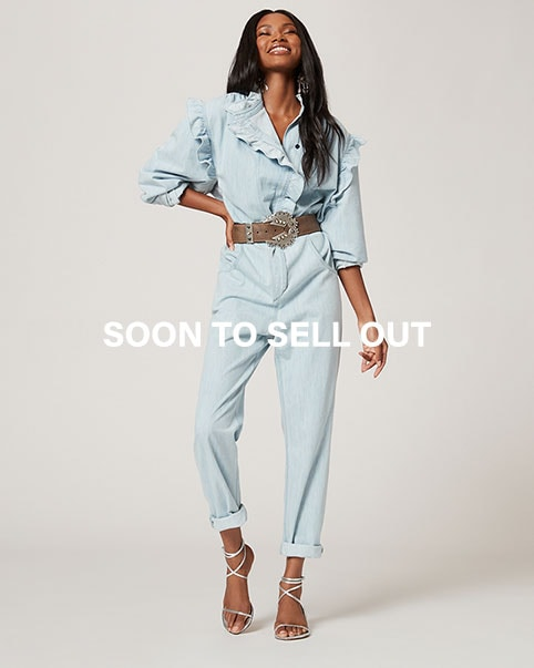 A model standing wearing a blue chambray jumpsuit with a ruffle collar and brown belt. Soon to Sell Out. Shop Now.