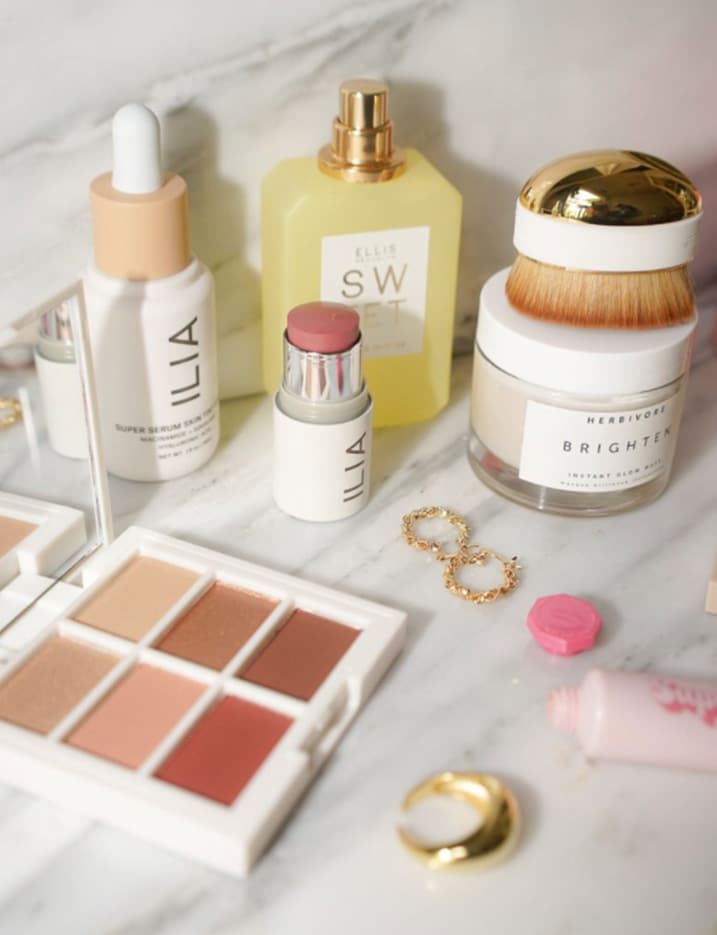 A variety of skincare and makeup products featuring clean beauty brands are scattered on a marble countertop. Shop Clean Beauty.