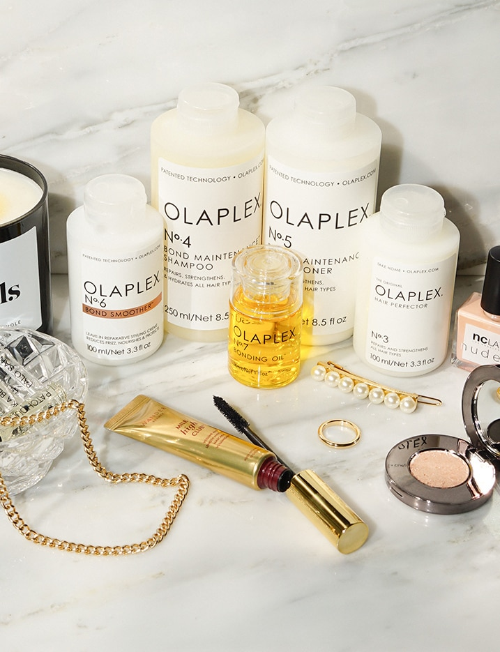 A variety of hair care products and accessories are displayed on a marble countertop featuring bottles from the haircare brand Olaplex. Shop Haircare.