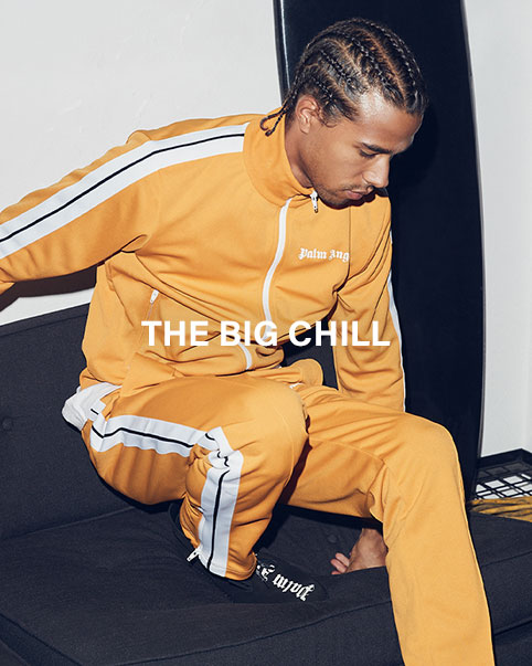 A model posing on a couch wearing a matching yellow Palm Angels tracksuit and socks. Shop Leisure.