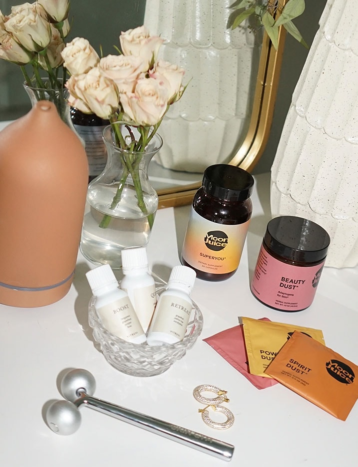 Wellness products like Moon Juice supplements sit on top of a beauty vanity. Shop Wellness.
