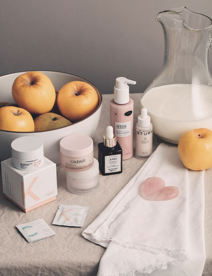 A display of skincare products sit on a canvas table cloth next to a pitcher of milk and a bowl of apples and pears. Shop Skincare Essentials.