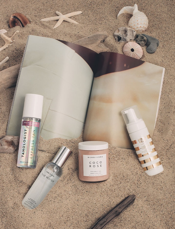 A variety of self-tanners and tanning skincare products sit in the sand with a magazine and seashells. Shop Beach-Ready Bronze.