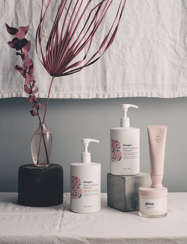 Haircare products are displayed on a canvas covered table cloth with concrete stones and rocks and a vase of burgundy fronds. Shop Hair Game-Changers.