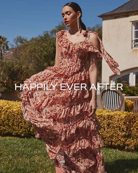 A model standing in front of bushes wearing a white sleeveless midi dress and white heels. A model wearing a pink floral print maxi dress with shoulder ties and tiered ruffles. The back of a model standing on a staircase wearing a white lace gown with a criss-cross back. A model wearing a bronze sleeveless midi dress with wrap styling and tan sandals. Happily Ever After. Shop the Edit.