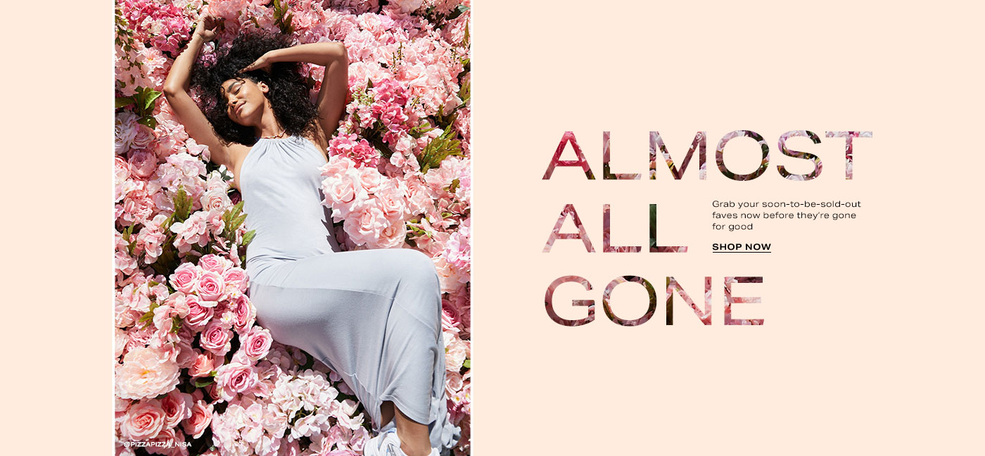 Naressa Valdez lying in a bed of pink flowers wearing a light blue maxi dress with a halter neckline. Almost All Gone. Shop Now.