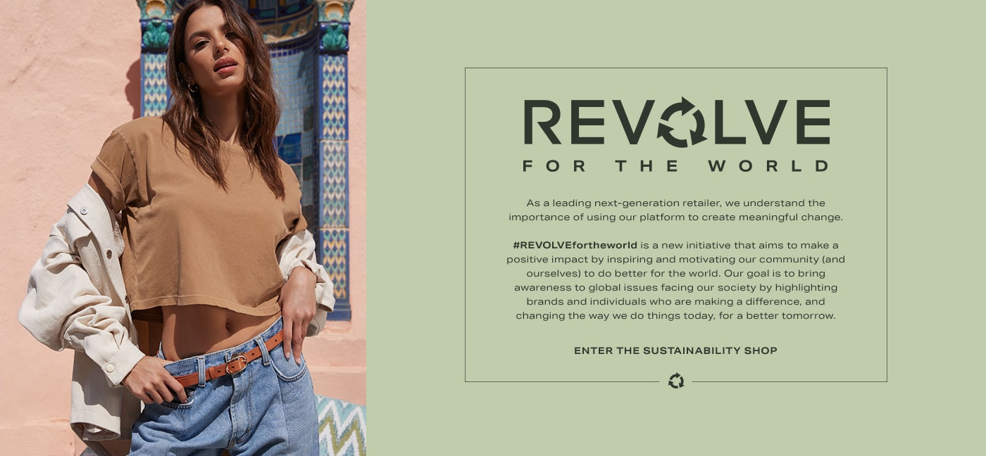 A model wearing a brown cropped tee shirt, a cream colored button down shirt, and blue jeans with a brown belt. REVOLVE for the World. Enter The Sustainability Shop