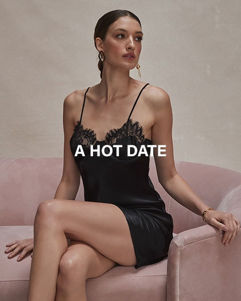 Model is sitting on a pink sofa wearing a black lace slip dress.  A Hot Date: The cutest little looks to wear for your next date, no matter if you're staying in or going out. Shop The Edit.