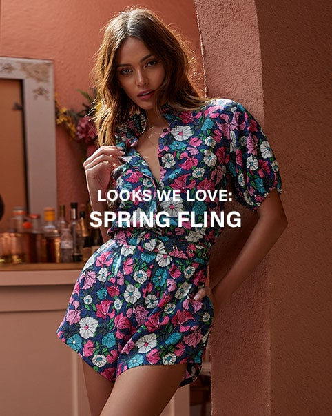 A model wearing a pink and yellow floral print one piece swimsuit with shoulder tie details and a ruffle trim. A model wearing a blue, pink, and white floral print short sleeve romper. A model wearing sunglasses a white graphic print sweatshirt, purple ruffle shorts with a black belt, and carrying a white clutch. Looks We Love: Spring Fling. Shop the Edit.