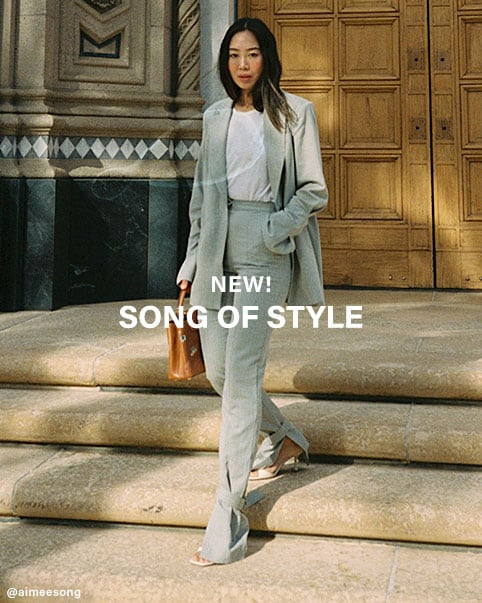 Aimee Song wearing a blue ribbed short sleeve sweater with a tie neckline and matching blue pants. Aimee Song walking down steps wearing a white top, beige blazer, matching pants with tie ankle details, and white heels. Aimee Song wearing a white top, beige blazer, brown leather jacket, matching beige pants with tie ankle details, and white heels. Aimee Song holding a coffee cup wearing a brown oversized cable knit turtleneck and brown wide leg pants. NEW! Song of Style. Shop the Collection.