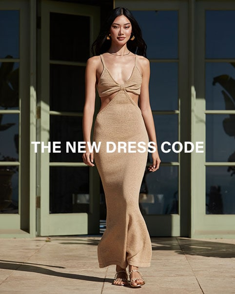A model standing outside wearing a gold maxi dress with side cut-outs. The New Dress Code. Shop the Edit.