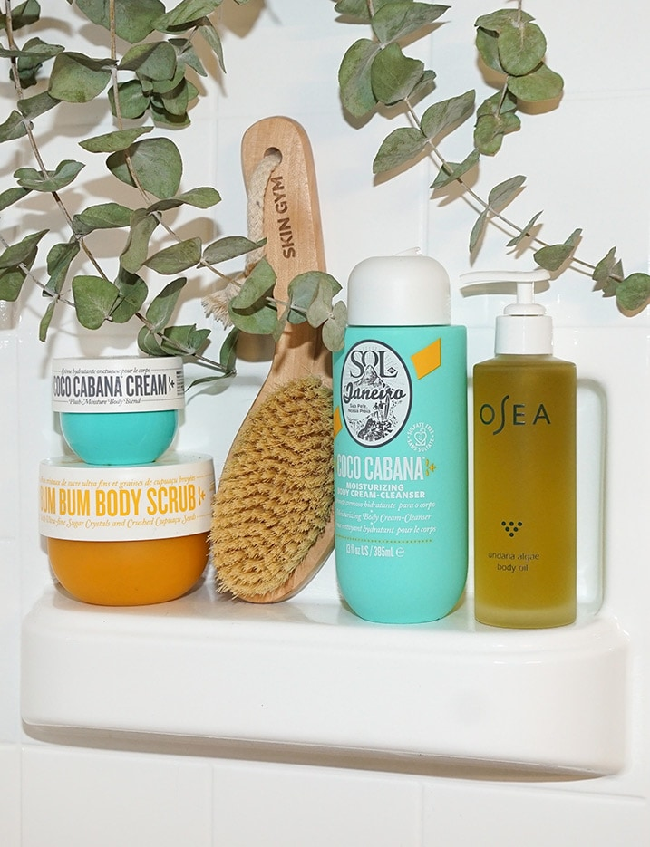 Various bath products sit on a bathtub shelf.Shop Bath & Body.