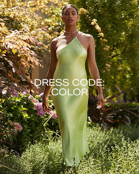 A model standing in grass in front of a flower bush wearing a green one shoulder slip dress. Dress Code: Color. Shop the Edit.