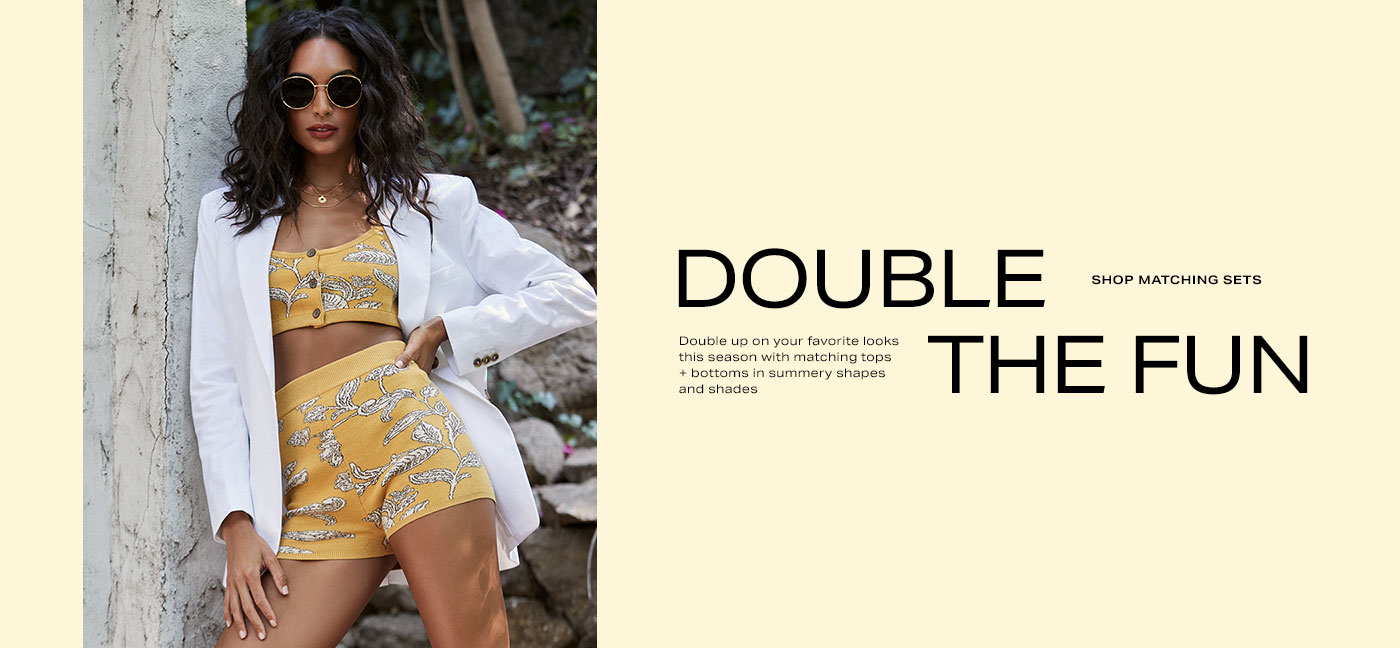 A model wearing sunglasses, a white blazer, a yellow crop top with white leaf print and matching high waist shorts. Double the Fun. Shop Matching Sets.