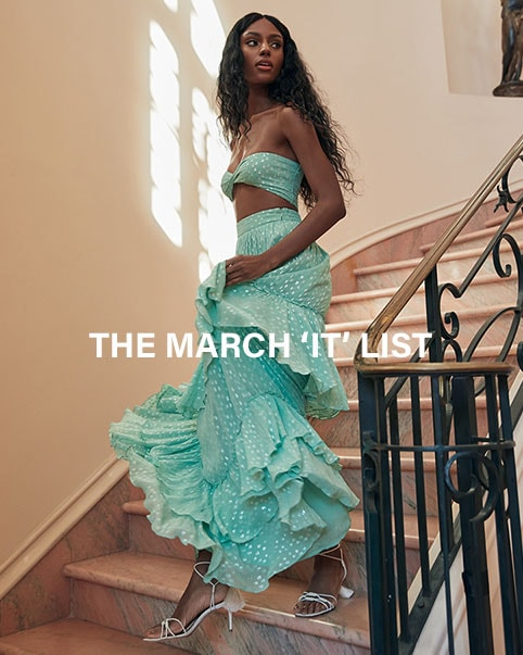 A model wearing a cream tank top with strappy details and white, blue, and red paisley print high waist shorts. A model wearing a turquoise strapless crop top and a matching high waist maxi skirt with tiered ruffles. A model wearing a sleeveless white jumpsuit with a pink and yellow floral print. The March 'It' List. Shop the Edit.