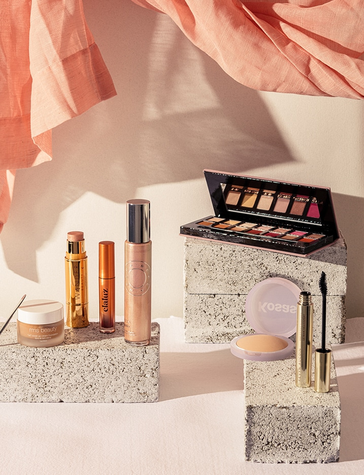 A variety of makeup products sit on stone blocks with a peach-toned linen drape floating lightly above. Shop Makeup.