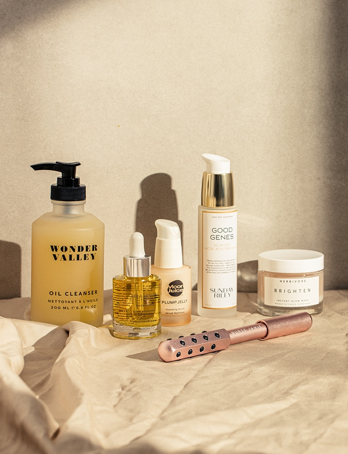 A variety of skincare products sit on a sand toned cloth against a sandstone wall.