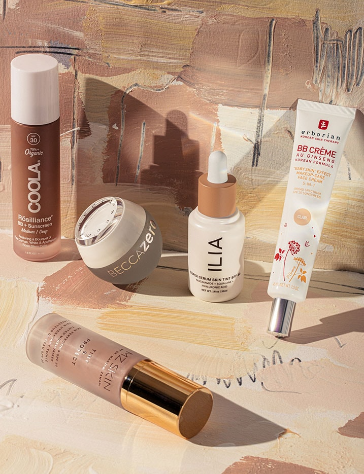 Brown and cream tone packaged BB Cream products sit on cream paper with various brush strokes of different shades of brown.