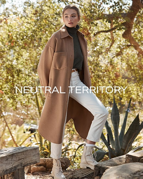 A model standing in front of a tree wearing a green turtleneck, a tan coat, white pants, and beige boots. A model sitting on a couch wearing a sleeveless green dress. Neutral Territory. Shop the Edit.