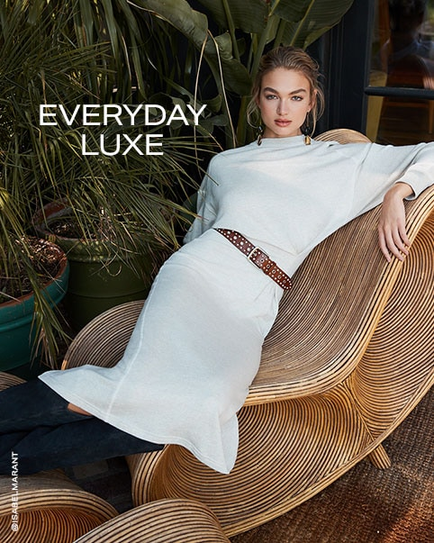 A model wearing a black top, black leather shorts, a brown cape, and black knee-high boots. A model lying on a chair wearing a white long sleeve knit dress with a brown belt. Everyday Luxe. Shop the Edit.