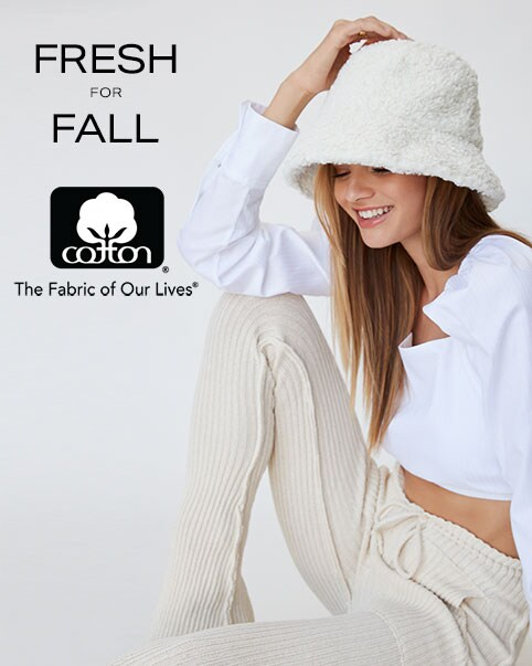 A model wearing a white fuzzy bucket hat, a white long sleeve top, and beige drawstring pants. Fresh for Fall. Enter The Cotton Shop.