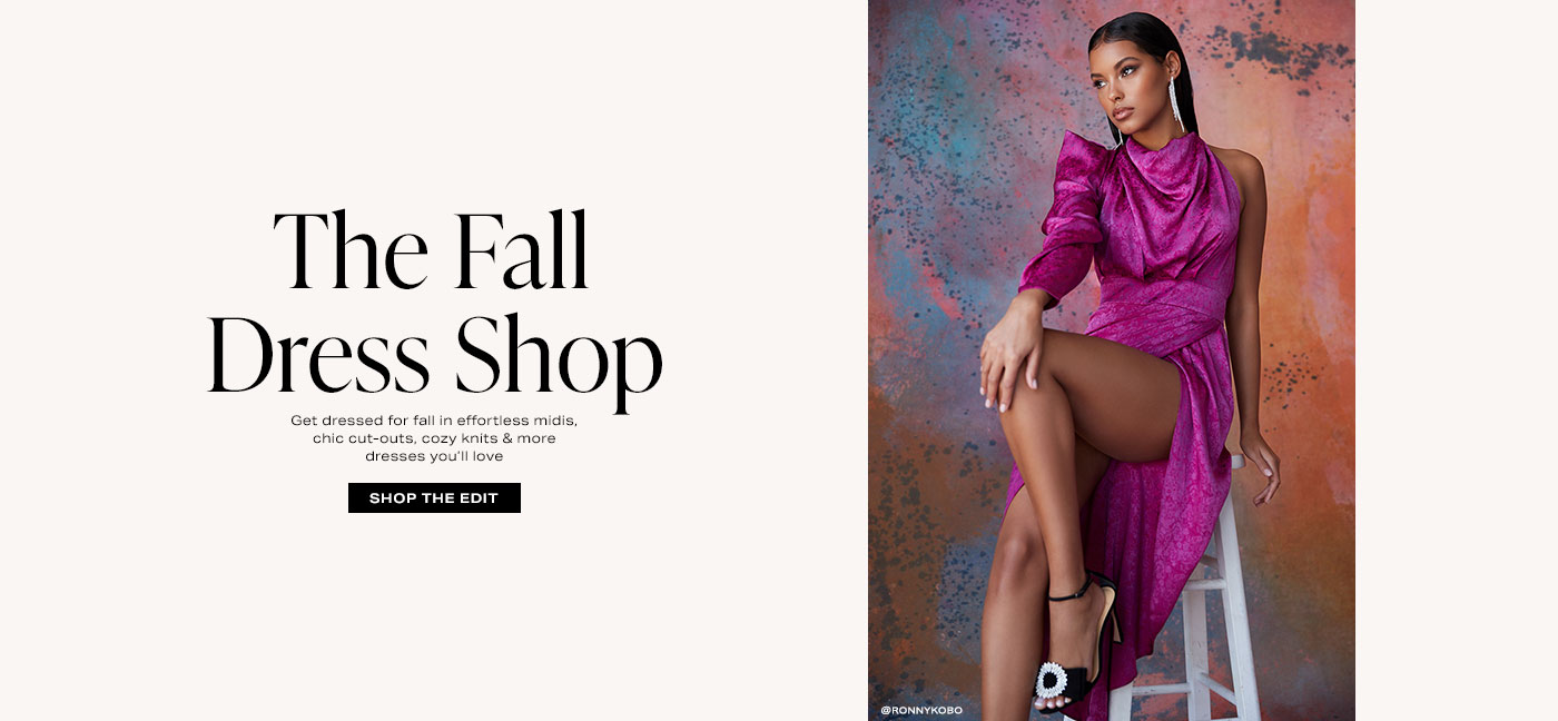 A model sitting on a stool wearing a purple one shoulder dress with a long sleeve and jacquard print and black heels. The Fall Dress Shop. Shop the Edit.